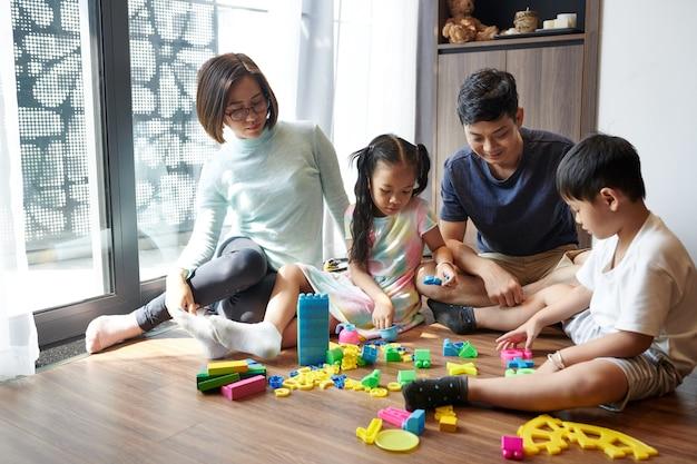 Aziatische ouders en kinderen die thuis samen spelen met plastic figuren en kleurrijke bouwstenen