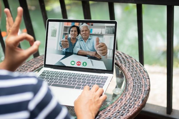 Aziatische ouders zijn videoconferentie met dochter tijdens vakantie