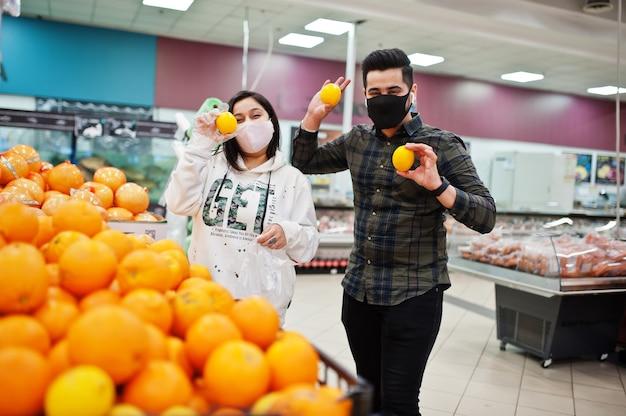 Aziatische paar dragen in beschermend gezichtsmasker samen winkelen in de supermarkt tijdens pandemie. verschillende soorten fruit kiezen.