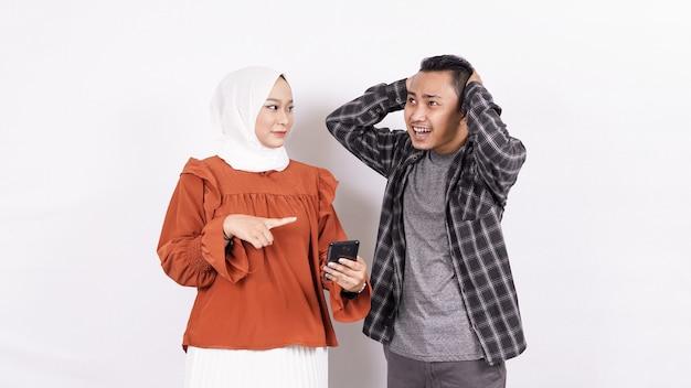 Aziatische paar jongen geërgerd expressie en meisje holdinh telefoon