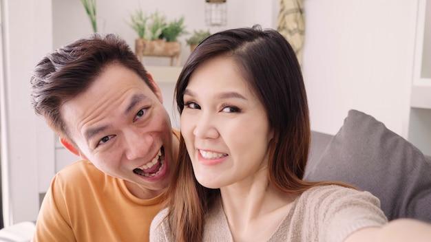 Aziatische paar met behulp van smartphone video bel met vriend in de woonkamer thuis
