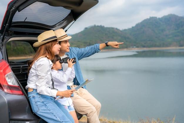Aziatische paar met een kaart zitten in de achterkant van de auto