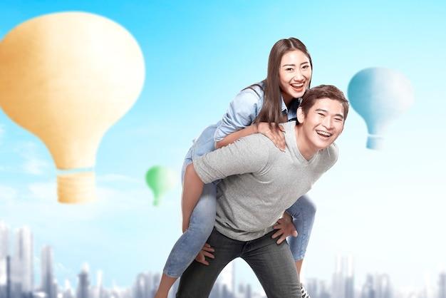 Aziatische paar plezier met kleurrijke luchtballon vliegen met stadsgezicht achtergrond