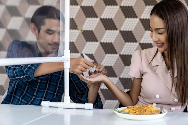 Aziatische paar schoonmakende hand vóór maaltijd, het nieuwe normale uit eten.