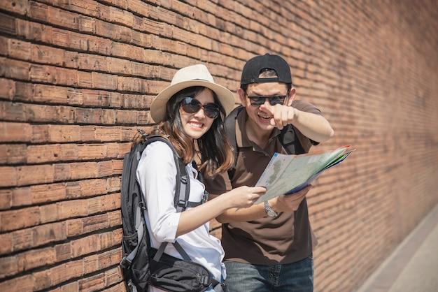 Aziatische paar toeristische kaart van de stad te houden van de weg