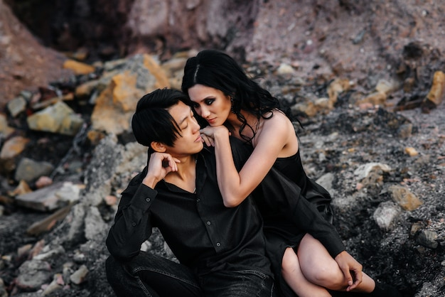 Aziatische paar verliefd knuffels zittend op de rotsen. liefdesverhaal