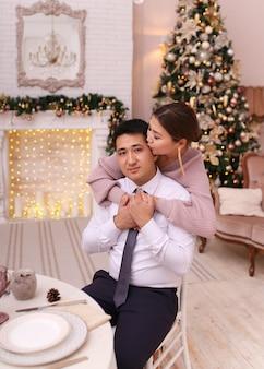 Aziatische paar verliefd man en vrouw in elegante outfits zitten bij open haard en boom, kerstdiner