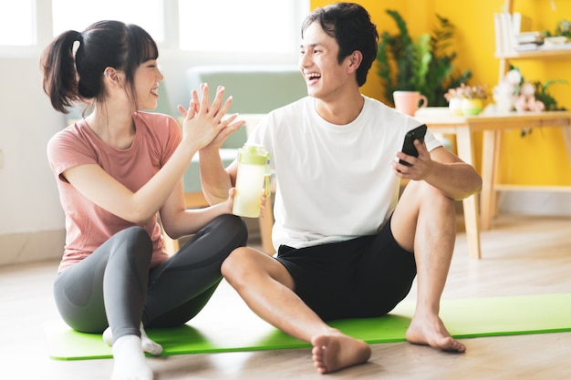 Aziatische paar zitten en chatten na sportschool