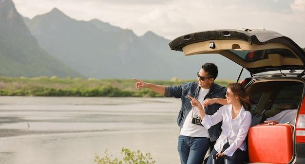 Aziatische paarman met uitstekende camera en vrouwenzitting op rug van autoreis naar berg en meer in vakantie met autoreisreis