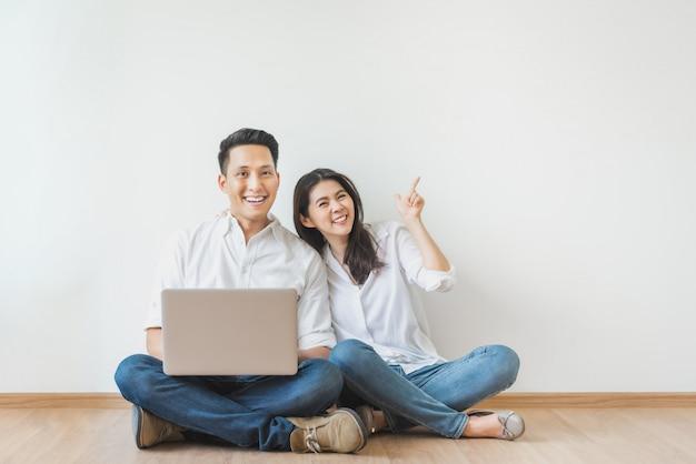 Aziatische paarzitting op vloer die laptop in witte ruimte met behulp van