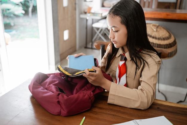 Aziatische padvindingsstudent die alvorens naar school te gaan voorbereidingen treft
