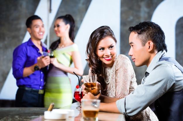 Aziatische paren die bij nachtclubbar flirten en drinken