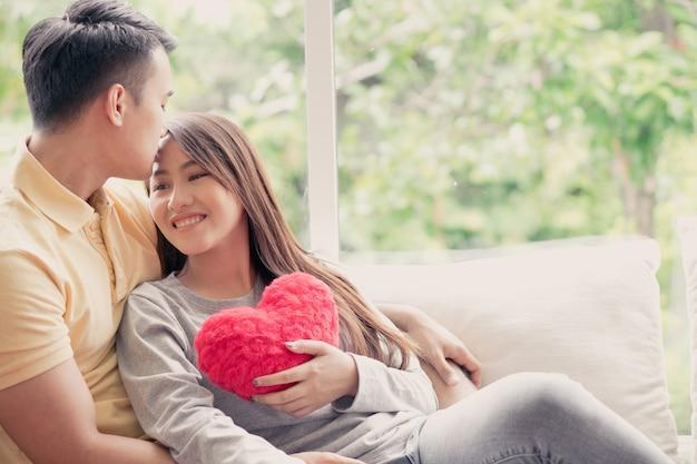 Aziatische paren die op de bank zitten waarin vrouwen een rood hart houden en gelukkig glimlachen.