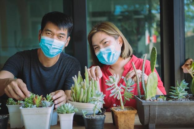 Aziatische paren succulente planten thuis tijdens covid-19 crisis