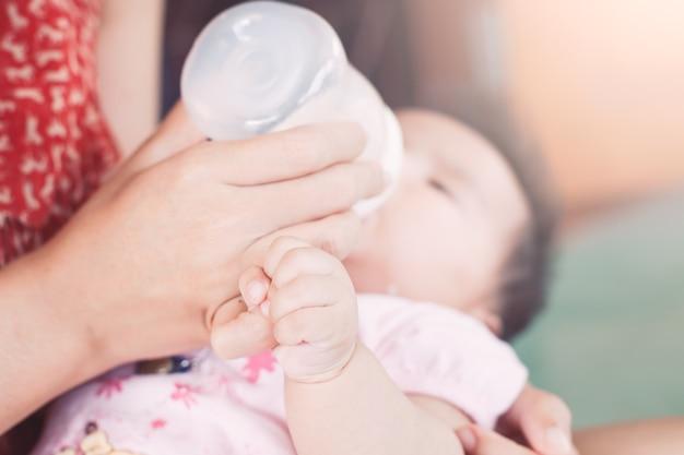 Aziatische pasgeboren baby meisje met moeders vinger