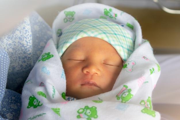 Aziatische pasgeboren baby was na het baden in een doek gewikkeld