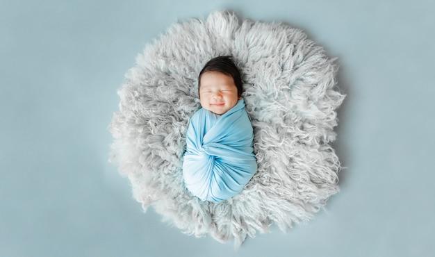 Aziatische pasgeboren babyslaap op bont