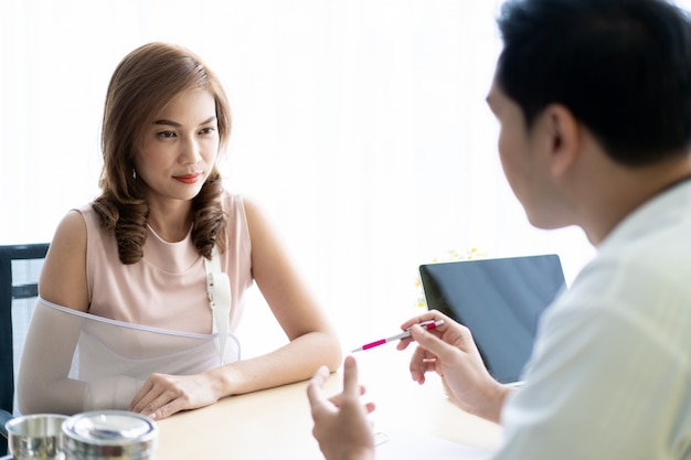 Aziatische patirntvrouw die aan de arts voor haar gezondheidsonderzoek, concept gezondheidszorg en wellness in het moderne leven spreekt.