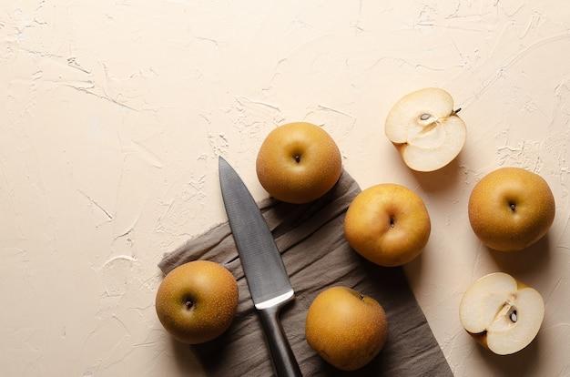 Aziatische peren met een zilveren mes en een bruin servet