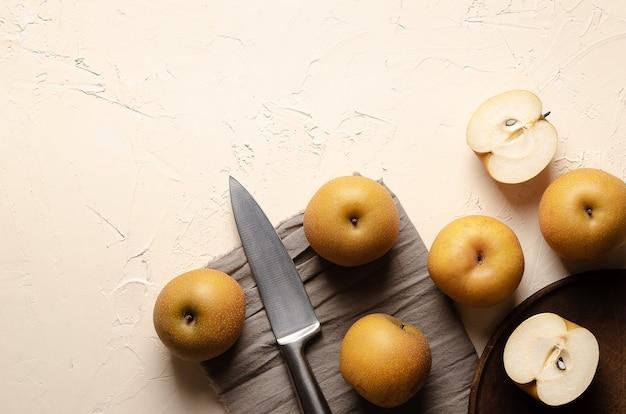 Aziatische peren met een zilveren mes en een stuk doek op een lichte achtergrond