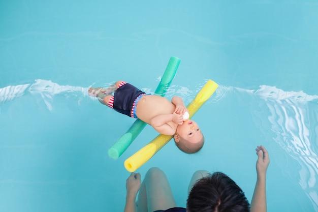 Aziatische peuter kind leren te drijven in het zwembad met zijn vader