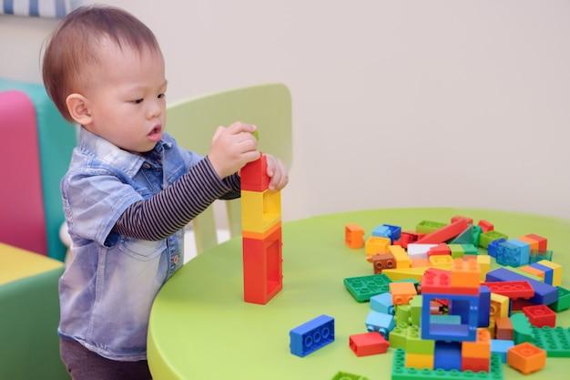 Aziatische peuterjongen die pret het spelen met kleurrijke plastic blokken hebben binnen op school spelen