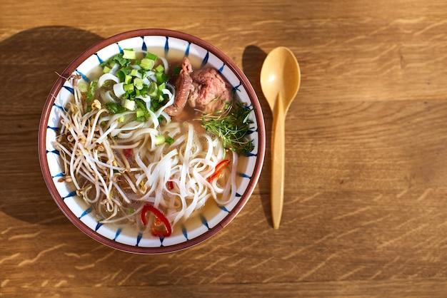 Aziatische pho bo-soep, beste pho-bouillon, in een lichte kom op een houten tafel, bovenaanzicht