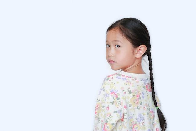 Aziatische portretten weinig kindmeisje die camera van achtereind kijken dat op witte achtergrond met exemplaarruimte wordt geïsoleerd