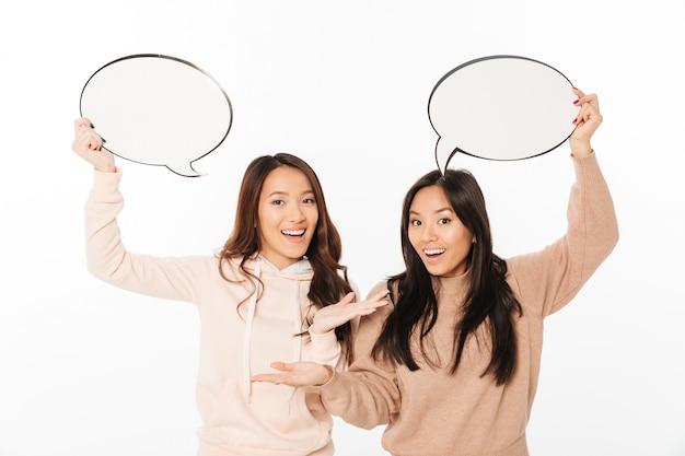 Aziatische positieve dameszusters die toespraakbellen houden.