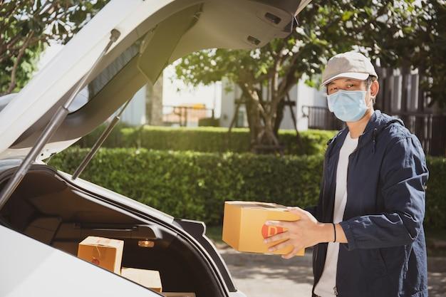 Aziatische postbode met een hygiënisch beschermend gezichtsmasker die een pakketpakket opneemt