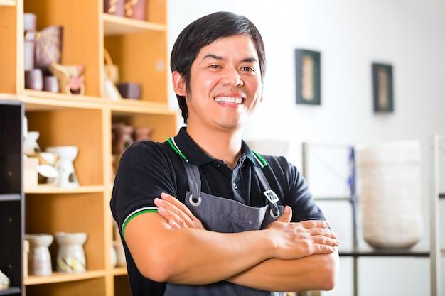Aziatische potter in zijn winkel die souverniers verkoopt