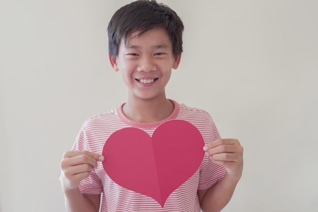 Aziatische pretwen jongen die groot rood hart, hartgezondheid, schenking, gelukkige vrijwilligersliefdadigheid, sociale verantwoordelijkheid, wereldhartdag, wereldgezondheidsdag, werelddag van de geestelijke gezondheid, welzijn, hoopconcept houdt
