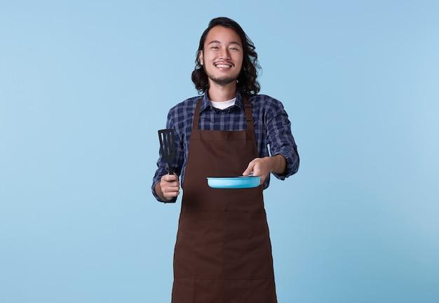 Aziatische professionele chef klaar om te koken, chef-kok met spatel en koekenpan geïsoleerd op blauwe achtergrond.