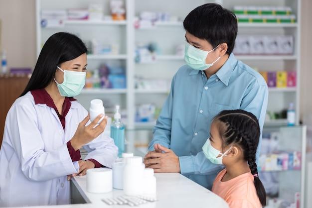 Aziatische professionele jonge vrouwenapotheker die gezichtsmasker draagt terwijl het voorschrijven van medicijnen aan de klant bij het concept van drogisterij thailand covid-19