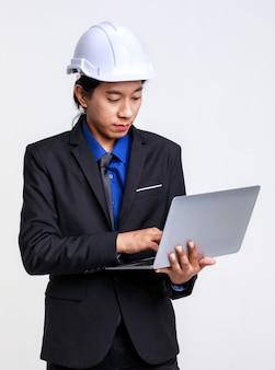 Aziatische professionele succesvolle mannelijke voorman industrieel ingenieur in zwart formeel pak en veiligheidshelm staande op een witte achtergrond.
