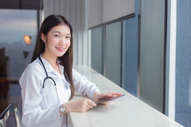 Aziatische professionele vrouwelijke arts gekleed in een witte medische jas zit op een stoel in een ziekenhuisbibliotheek om wat informatie op een tablet te zoeken voor behandeling in het zorgconcept.