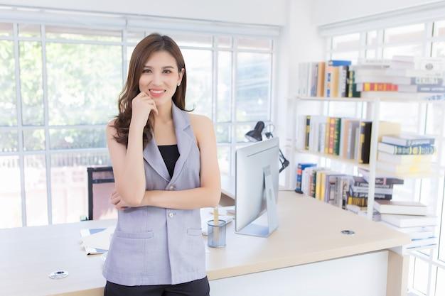 Aziatische professionele werkende vrouw met lang haar die ze kruist en gelukkig glimlacht. werk vanuit huis.