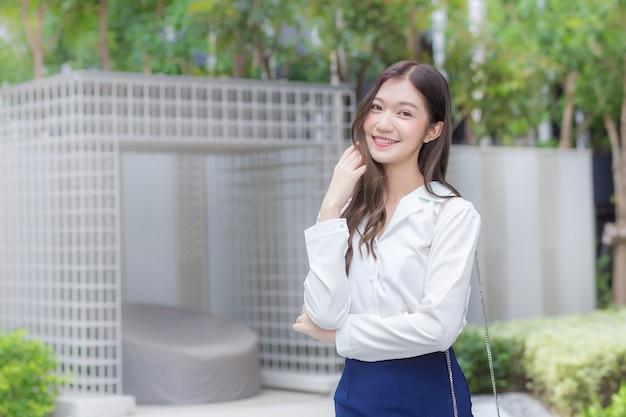 Aziatische professionele zakenvrouw draagt een wit overhemd en glimlacht terwijl ze naar haar werk gaat.