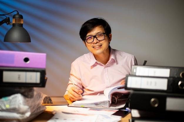 Aziatische projectmanager glimlacht en is blij met zijn baan. beroepsoverwerk. thaise freelancer doet deadline overwerkconcept. werk 's avonds laat.
