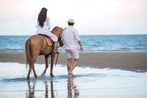 Aziatische reizende vrouw die een paard berijdt en let met zijn jongensvriend op zee strand.