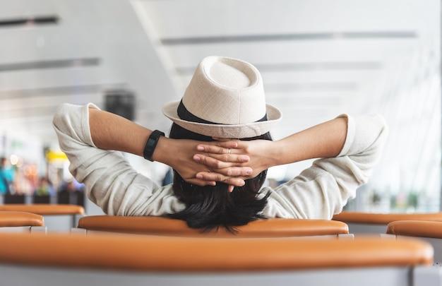 Aziatische reiziger is ontspannen tijdens het wachten op de vlucht op de luchthaven.