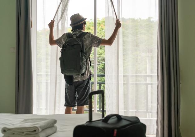 Aziatische reizigersmannen zien het uitzicht op het terras van het hotel