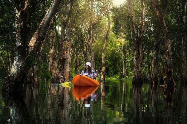 Aziatische reizigersvrouw die in mangrovebos van botanische tuin thailand kajakken