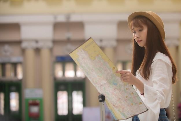 Aziatische reizigersvrouw die kaart station bekijken