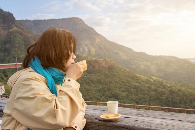 Aziatische reizigersvrouw die met sjaal een kop van espressokoffie drinken en van aardmening van het berglandschap in de ochtend met zonlicht genieten