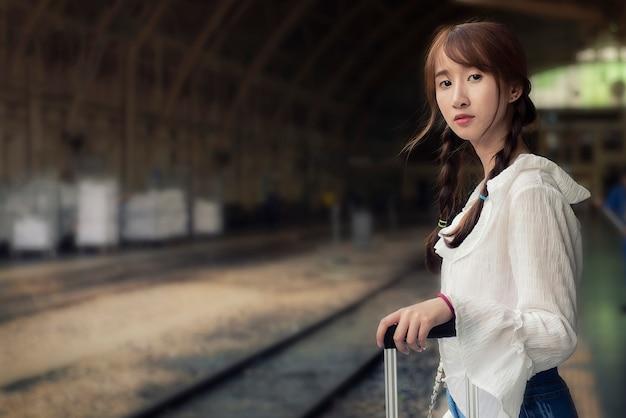 Aziatische reizigersvrouw die op reis op spoorwegplatform wachten