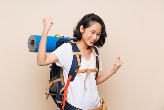 Aziatische reizigersvrouw die over geïsoleerde muur een overwinning viert