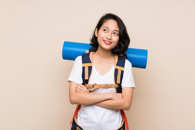 Aziatische reizigersvrouw die over geïsoleerde muur omhoog terwijl het glimlachen kijkt