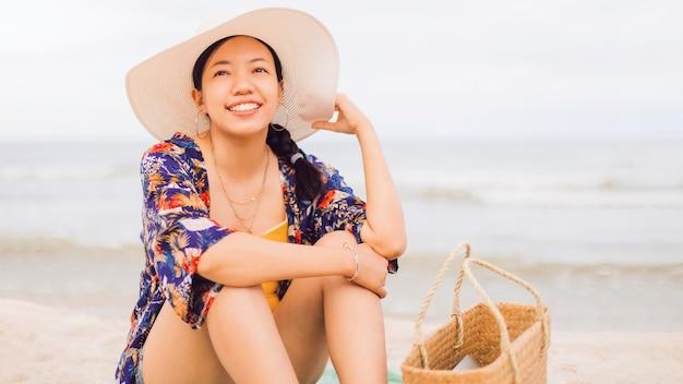 Aziatische reizigersvrouw leun achterover en ontspan op het strand aan zee tijdens een weekendvakantie