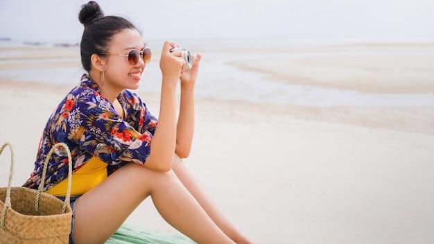 Aziatische reizigersvrouw leun achterover en ontspan op het strand aan zee